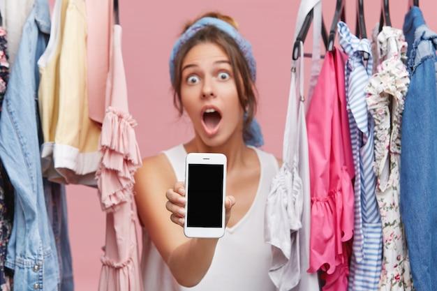 Aantrekkelijke vrouwelijke shopaholic mobiele telefoon met een leeg scherm, met schokkende verkoopprijzen op kledingwinkel website tijdens het online winkelen