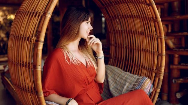 Aantrekkelijke vrouwelijke situering in hangende bamboetrap op openluchtveranda van houten bungalow
