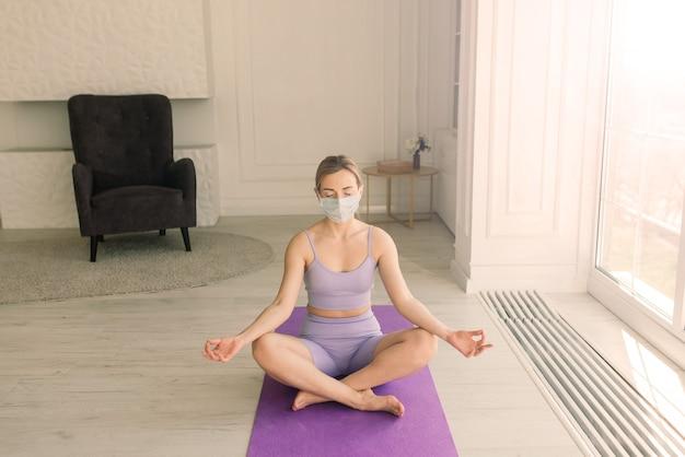 Aantrekkelijke vrouwelijke sportfitnesscoach met een wit medisch masker doet oefeningen op yogamat thuis.
