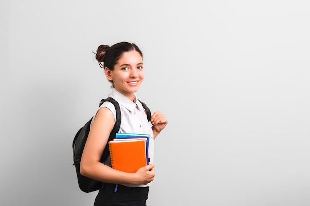 Aantrekkelijke vrouwelijke student met kuiltjes in wangen die holdingsnotitieboekjes in één hand glimlachen en rugzak op schouders met leuke gezichtsuitdrukking