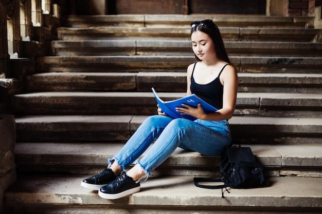 Aantrekkelijke vrouwelijke student zittend op trappen in de campus
