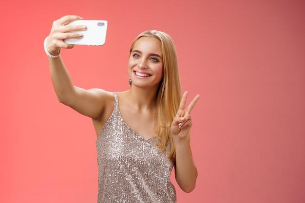 Aantrekkelijke vrouwelijke tedere jonge blonde meid 25s in zilveren stijlvolle jurk die selfie neemt, arm uitsteekt toon vredesgebaar smartphone display record video groet internetfans, staande rode achtergrond.
