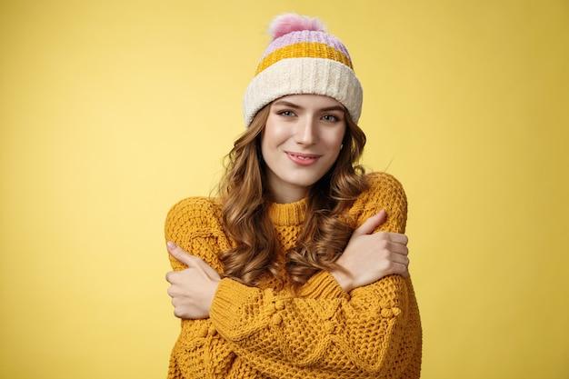 Aantrekkelijke vrouwelijke tedere jonge vrouw voelt zich gezellig en omhelst zichzelf glimlachend opgetogen schattig draagt...