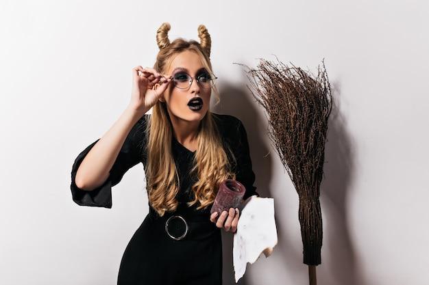 Aantrekkelijke vrouwelijke tovenaar gek rond tijdens halloween fotoshoot. blonde blanke dame in heksenkostuum poseren op witte muur.