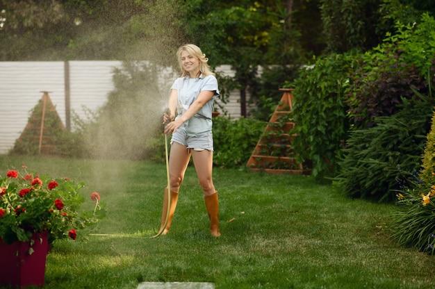Aantrekkelijke vrouwelijke tuinman met slang planten in de tuin water geven. vrouw zorgt voor bloemen buiten, tuinieren hobby, bloemist lifestyle en vrije tijd