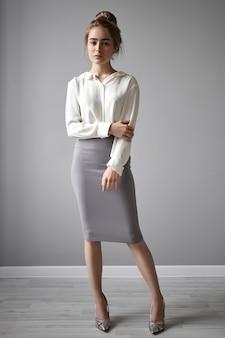 Aantrekkelijke vrouwelijke werknemer met haar knoop poseren geïsoleerd tegen grijze muur achtergrond, serieus kijken, gekleed in elegante formele kleding. verticaal schot van doordachte jonge onderneemster