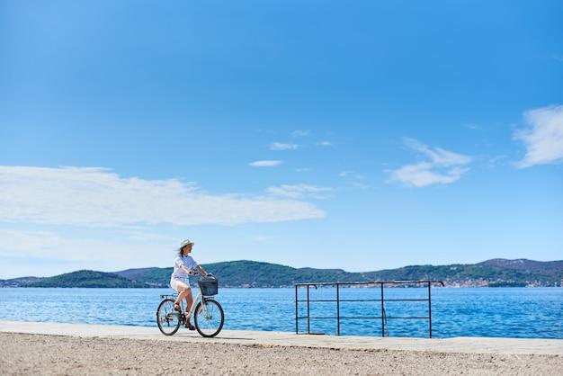 Aantrekkelijke vrouwen berijdende fiets langs steenachtige stoep onder duidelijke blauwe hemel op fonkelend zeewater en bergenmening over tegenovergestelde kustachtergrond. toerisme en vakanties.