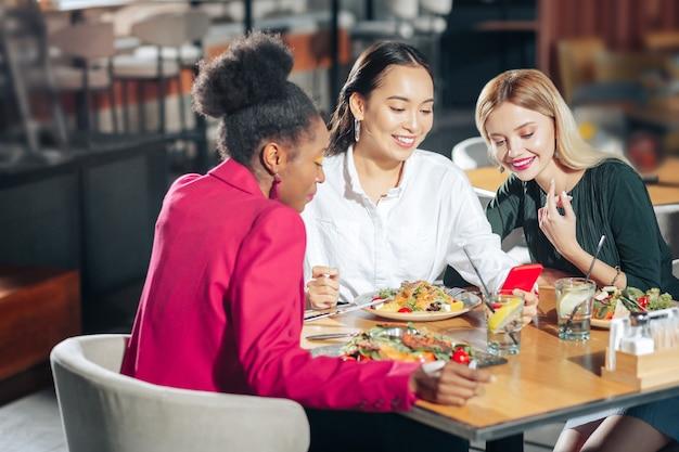 Aantrekkelijke vrouwen drie aantrekkelijke jonge vrouwen die gezonde salades eten en video kijken