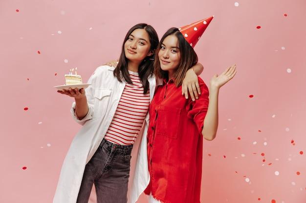 Aantrekkelijke vrouwen in stijlvolle oversized shirts poseren met een stuk verjaardagstaart op roze geïsoleerde muur met confetti