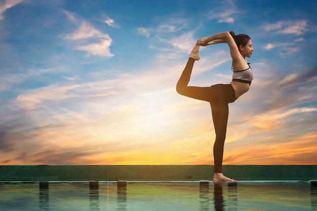 Aantrekkelijke vrouwen spelen yoga. bij het zwembad voor haar goede gezondheid