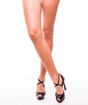Aantrekkelijke vrouwenbenen in muilezels die op witte studioachtergrond worden geïsoleerd
