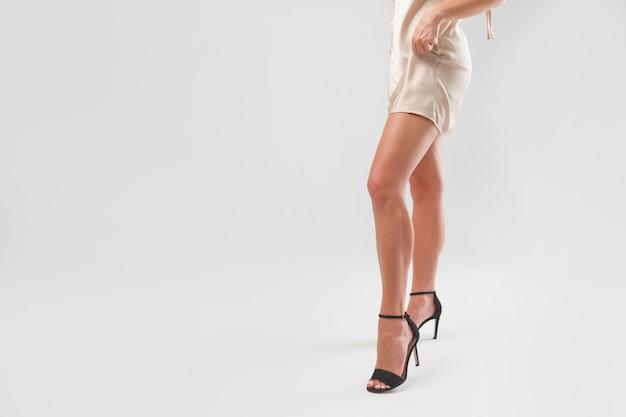 Aantrekkelijke vrouwenbenen op hoge hielen in nachtjapon zijde. sierlijke vrouwelijke figuur in lingerie.