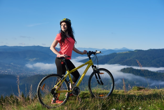 Aantrekkelijke vrouwenfietser met gele fiets op een landelijke sleep in de bergen, genietend van ochtendnevel in vallei, bossen op vage achtergrond. buitensportactiviteiten