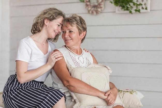 Aantrekkelijke vrouwenzitting met haar moeder op bank die elkaar bekijken