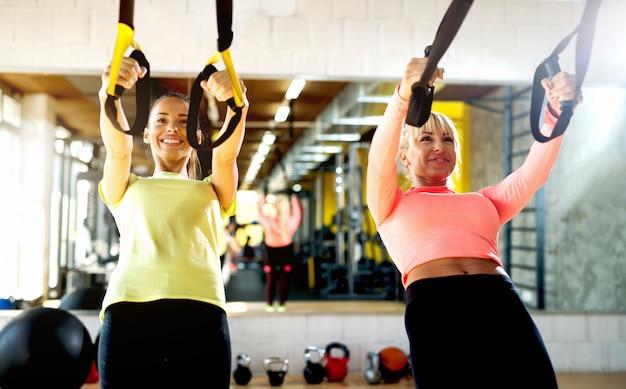 Aantrekkelijke vrouwtjes trainen in de sportschool.