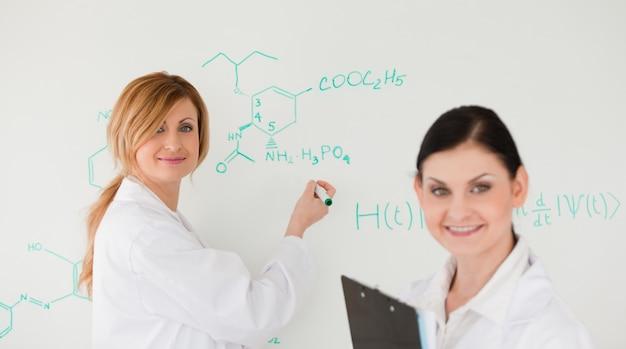 Aantrekkelijke wetenschapper die een formule schrijft die door haar assistent wordt geholpen