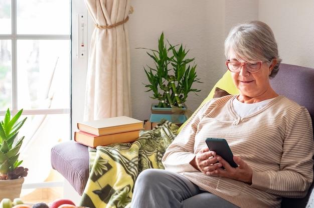 Aantrekkelijke witharige senior vrouw thuis zittend op de bank met haar smartphone