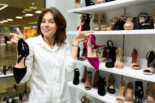 Aantrekkelijke witte vrouw kan niet beslissen welk paar hakken te kopen, met zwarte schoenen en paarse in haar handen.