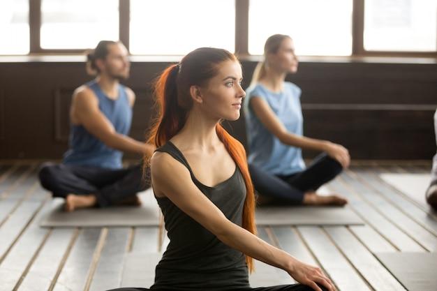 Aantrekkelijke yogi vrouw en een groep mensen in matsyendrasana