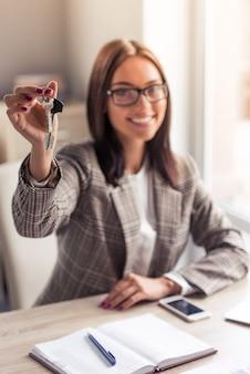 Aantrekkelijke zakelijke dame houdt sleutels van nieuwe flat.