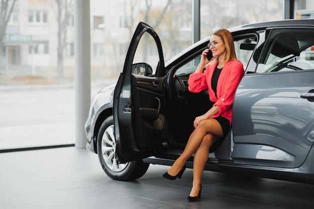 Aantrekkelijke zaken vrouw zitten in de auto, praten aan de telefoon en glimlachen
