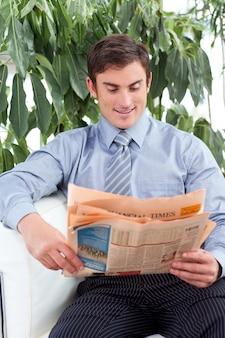 Aantrekkelijke zakenman die een krant op een bank leest