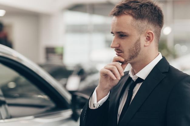 Aantrekkelijke zakenman die nieuwe auto koopt bij het handel drijven
