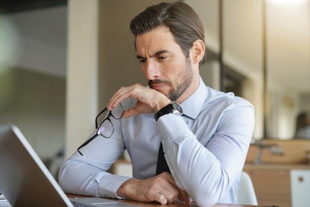 Aantrekkelijke zakenman die zich op laptop in bureau concentreert