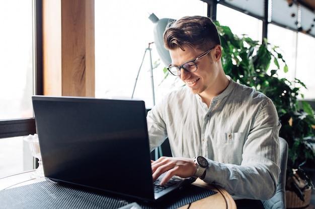 Aantrekkelijke zakenman in brillen die aan laptop, het typen, het besteden tijd bij koffie werken.