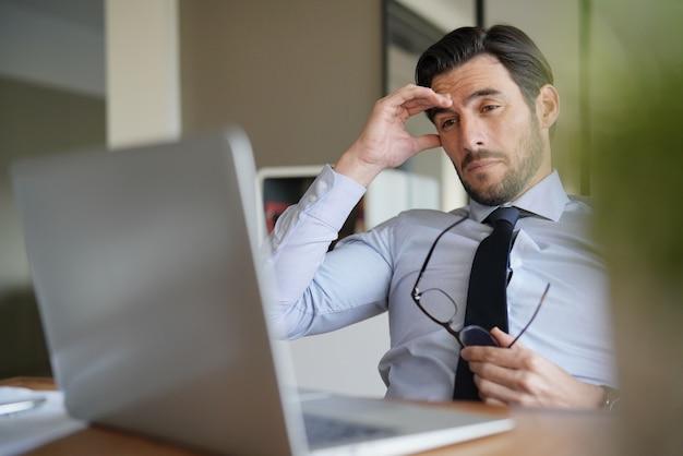 Aantrekkelijke zakenman kijken die die voor laptop ongerust wordt gemaakt en wordt vermoeid