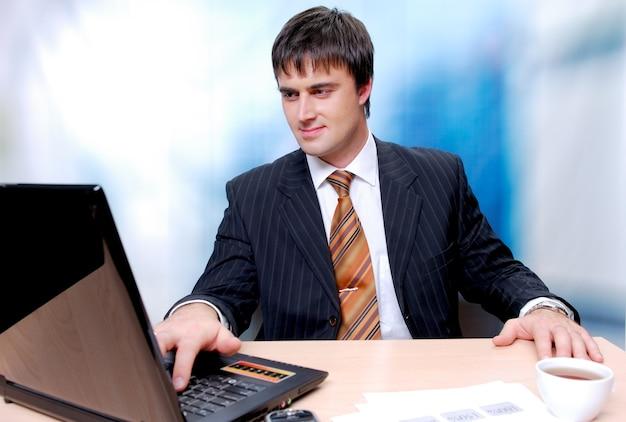 Aantrekkelijke zakenman zit aan de balie en werkt op een laptop