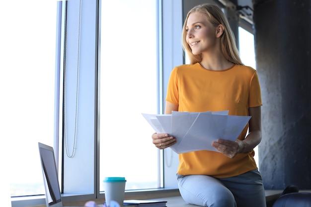 Aantrekkelijke zakenvrouw die documenten vasthoudt en ernaar kijkt terwijl ze op het bureau op kantoor zit.