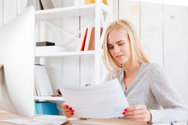 Aantrekkelijke zakenvrouw die documenten vasthoudt terwijl ze op haar werkplek zit