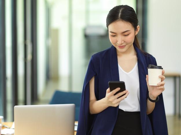 Aantrekkelijke zakenvrouw die koffie drinkt en een slimme mobiele telefoon gebruikt terwijl ze op kantoor staat, bericht van jonge zakelijke ondernemer met zakelijke leverancier op kantoor