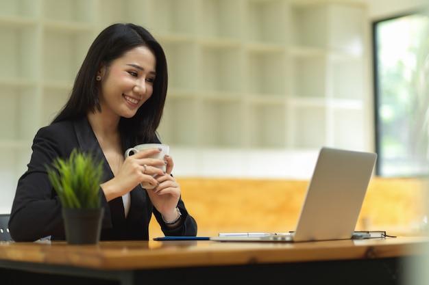 Aantrekkelijke zakenvrouw die koffie drinkt tijdens videoconferentie met zakenpartners