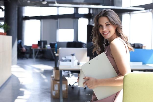 Aantrekkelijke zakenvrouw die naar de camera kijkt en glimlacht terwijl ze op kantoor staat.