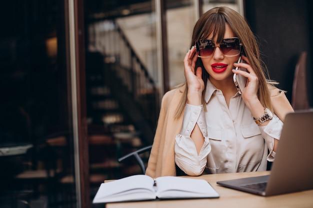 Aantrekkelijke zakenvrouw die op de computer in een café werkt