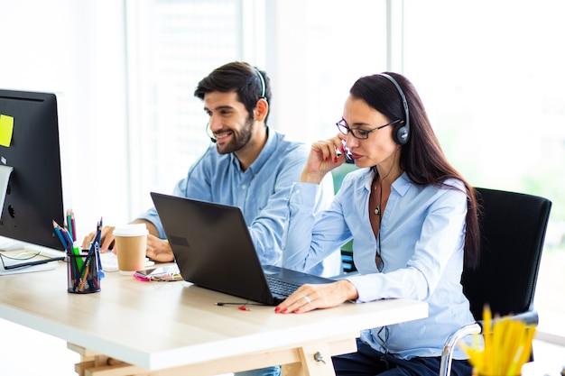 Aantrekkelijke zakenvrouw en zakenman met headsets glimlachen tijdens het werken met de computer op kantoor
