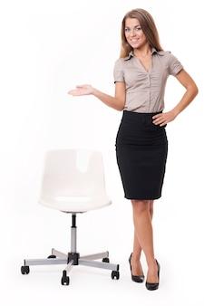 Aantrekkelijke zakenvrouw heet u welkom. ga zitten alstublieft