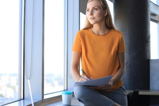 Aantrekkelijke zakenvrouw houdt documenten vast en kijkt weg terwijl ze op het bureau op kantoor zit.