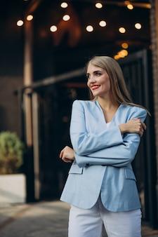 Aantrekkelijke zakenvrouw in blauwe jas bij het kantoorcentrum