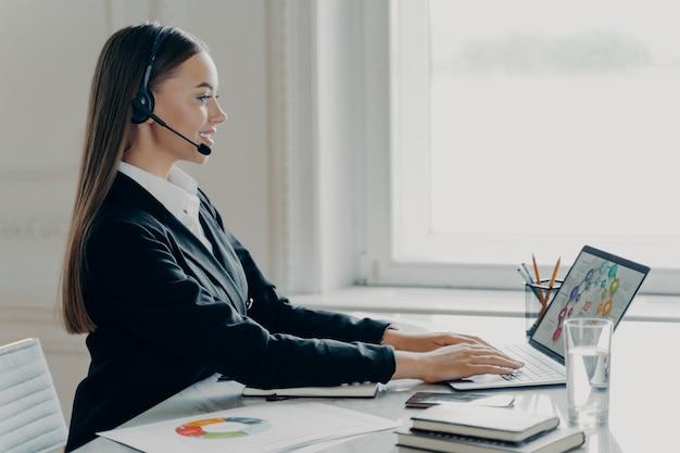 Aantrekkelijke zakenvrouw in een formeel pak met een headset met een videogesprek op een laptopcomputer, werkend met grafieken, zijaanzicht. tevreden jonge vrouwelijke econoom die online financieel rapport presenteert