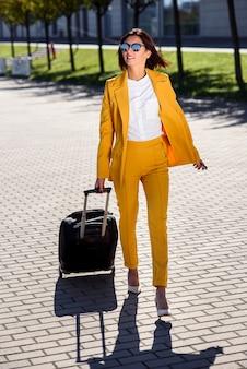 Aantrekkelijke zakenvrouw in stijlvolle gele pak trekt een koffer, haast zich naar een zakelijke bijeenkomst. aantrekkelijke bedrijfsvrouw die op een zakenreis gaat die haar koffer trekt langs de stoep achter haar.
