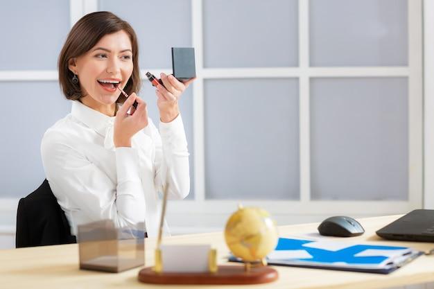 Aantrekkelijke zakenvrouw lip make-up doet op kantoor