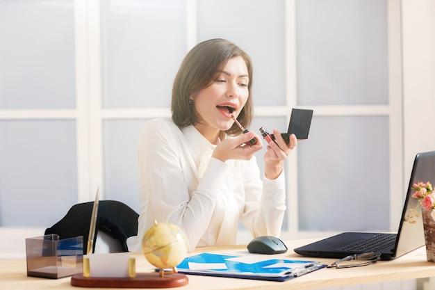 Aantrekkelijke zakenvrouw make-up doen op kantoor