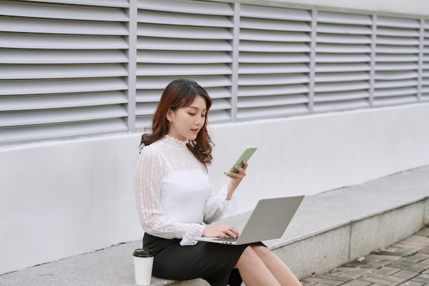 Aantrekkelijke zakenvrouw met behulp van een laptopcomputer zittend in een lommerrijke straat in de stad tijdens een zonnige dag, glimlachend.