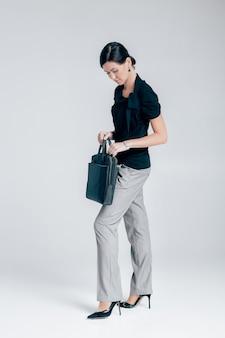 Aantrekkelijke zakenvrouw met een map met documenten op een grijze achtergrond