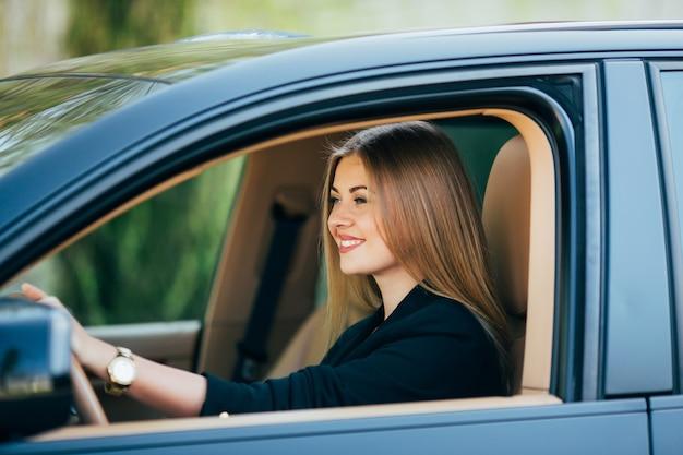 Aantrekkelijke zakenvrouw met zonnebril glimlachend en haar auto rijden.