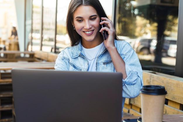 Aantrekkelijke zakenvrouw werken in café op open terras, laptop zit, praten over de telefoon.