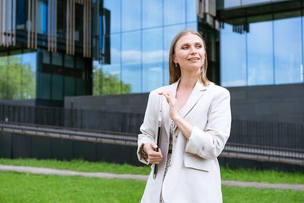 Aantrekkelijke zakenvrouw zakelijk succes charmante mooie vrouw houdt een laptop jonge vrouw...